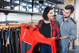 Young couple choosing touristic trousers in sports clothes store - 190960508