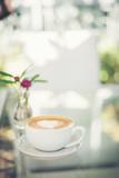 Latte art coffee with heart-shaped milk foam on table