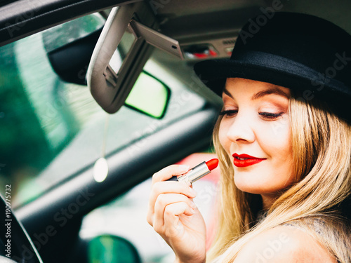 Young woman applying lipstick in car