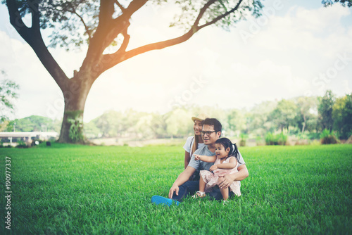 Happy young family spending time in the park, Father mother and daughter playing on the grass