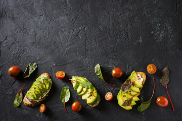 Some toasted with green avocado on black texture