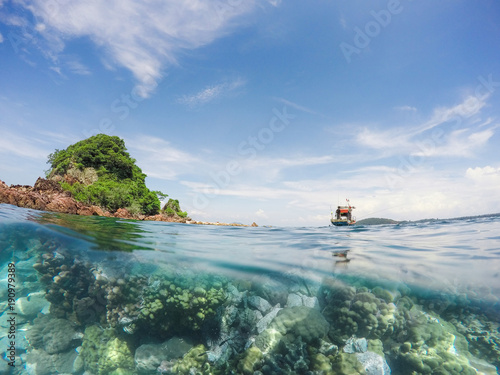 Fotobehang Thailand Fishing boat with small island in the sea over coral reef
