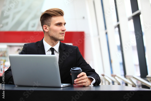 Young adult using laptop in airport lounge
