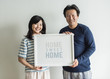 Asian couple holding home word in a frame