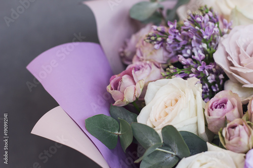 Lilac and eucalyptus in a large delicate bouquet on gray background