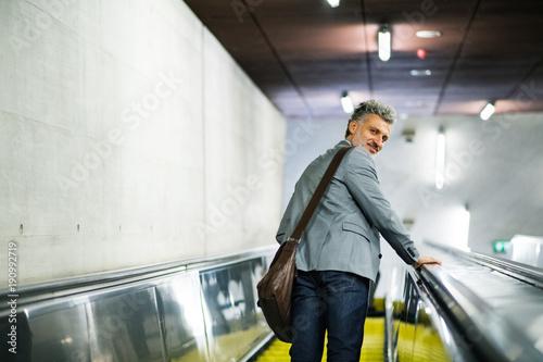 Businessman on an escalator on a metro station.