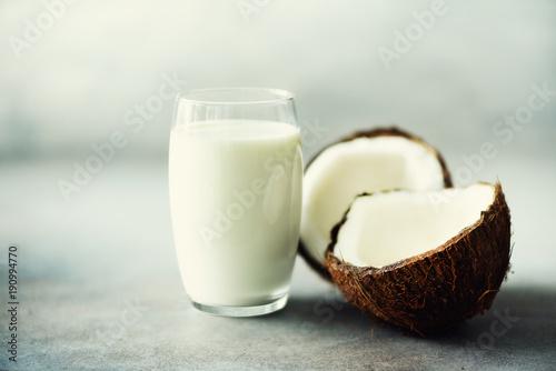 molkerei-der-kokosnuss-vegan-milch-nicht-in-den-glas-und-kokosnuss-fuit-halften-auf-grauem-konkretem-hintergrund-mit-kopienraum-vegetarisches-essen-konzept