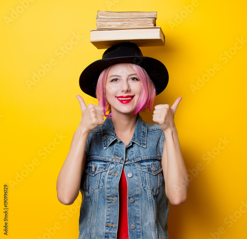 girl with pink hairstyle holding books over head