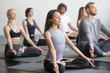 Leinwanddruck Bild - Group of young sporty people practicing yoga lesson with instructor, sitting in Padmasana exercise, Lotus pose, working out, indoor full length, students training in club, studio