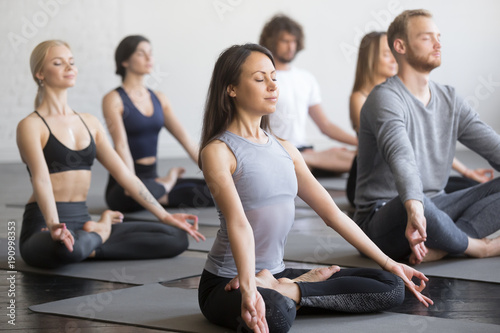 Leinwanddruck Bild Group of young sporty people practicing yoga lesson with instructor, sitting in Padmasana exercise, Lotus pose, working out, indoor full length, students training in club, studio