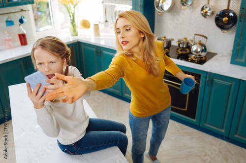 Anxious. Uncontrolled fair-haired slim girl holding a phone and crying while her mom taking it away