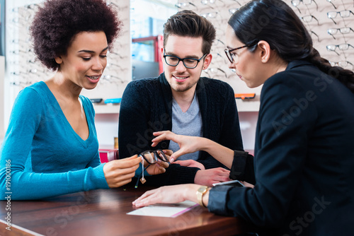 Woman and man buying glasses at optician store getting advice from saleslady