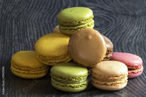 Foto op Aluminium Macarons Macarons de couleurs différentes en tas sur fond noir