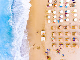 Sunbeds and umbrellas bird's eye view on sand beach in Greece