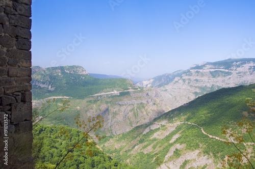 Fotobehang Olijf View of the green mountains blue sky, edge of a stone wall. Monastery Tatev, Syunik region, Armenia.