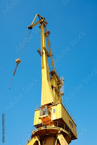 Yellow crane in a shipyard against the blue sky.