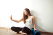 sports woman sitting on floor and making selfie on smartphone in fitness gym