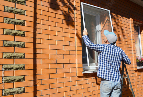 Worker installing mosquito net or mosquito wire screen on brick house window. - 191018573