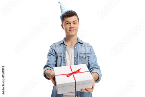 Teenager wearing a party hat giving a present