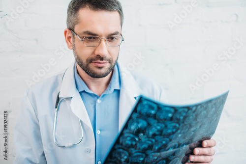 handsome adult doctor examining mri scan
