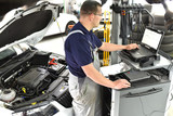 Mechaniker in der Autowerkstatt beim Softwareupdate mit einem Diagnosecomputer in der Werkstatt am Auto durch einen Mechaniker // Mechanic in the car repair shop during software update- 191027153