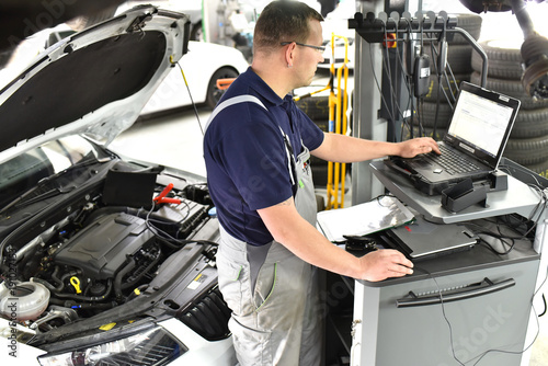 Poster Mechaniker in der Autowerkstatt beim Softwareupdate mit einem Diagnosecomputer in der Werkstatt am Auto durch einen Mechaniker // Mechanic in the car repair shop during software update