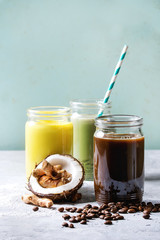Variety of iced colorful latte drinks. Iced coffee, turmeric and matcha latte cocktails in glass jars with ingredients above over grey green texture background. Copy space