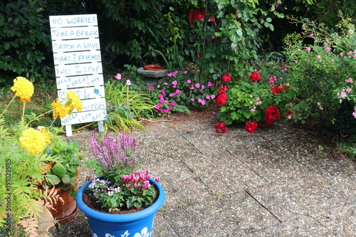 Cozy garden terrace surrounded by flowers and board with wise sayings
