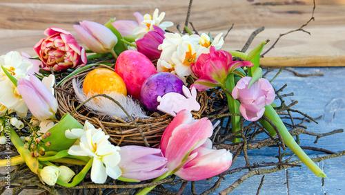 Leinwandbild Motiv Happy Easter: nest with Easter eggs, feathers, tulips and daffodils:)