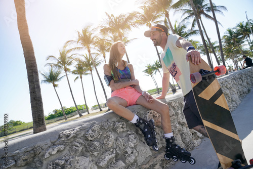Trendy young couple of skaters talking on Miami beach promenade
