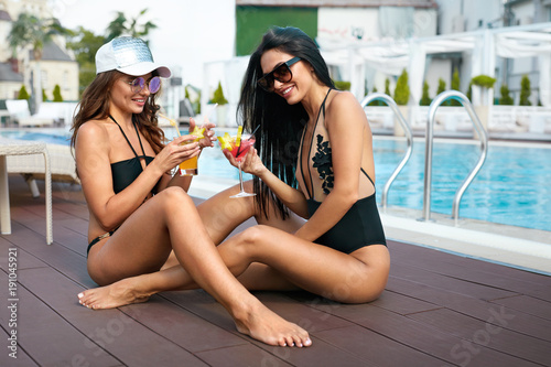 Summer Fun. Fashionable Girls Drinking Cocktails Near Pool.