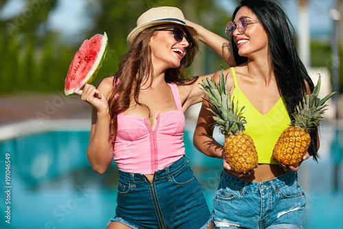 Summer Fun. Girls In Fashion Clothes With Fruits Near Pool