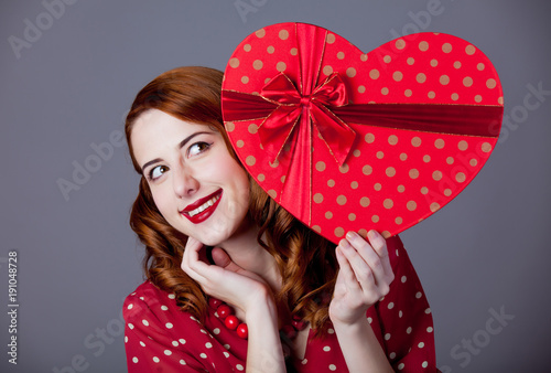 Girl in red polka dot dress with heart shape box for Valentine Day Holiday