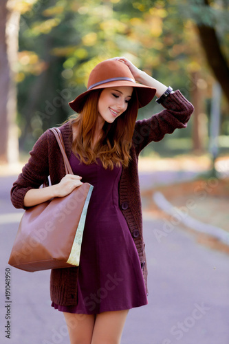 Young redhead woman with bag and hat