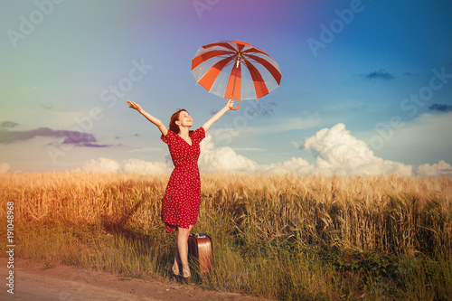 girl with umbrella and bag walking on road