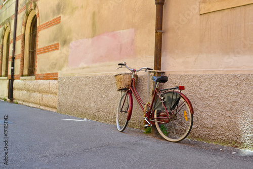Foto op Plexiglas Fiets Old bicycle with basket leaning against traditional building, Verona, Italy
