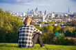 Back view of a tourist looking over London city skyline from Parliament Hill in Hampstead Heath