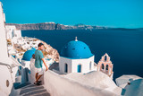 young man on vacation at Santorini Greece looking out over the blue ocean with old whitewashed buildings and a white blue greek church - 191053158