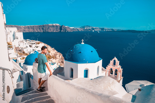 young man on vacation at Santorini Greece looking out over the blue ocean with old whitewashed buildings and a white blue greek church