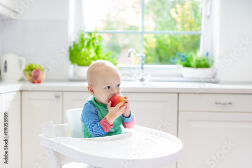 Baby boy eating apple in white kitchen at home - 191058989