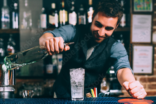 portrait of barman and close up details of preparation of alcoholic drink and cocktail