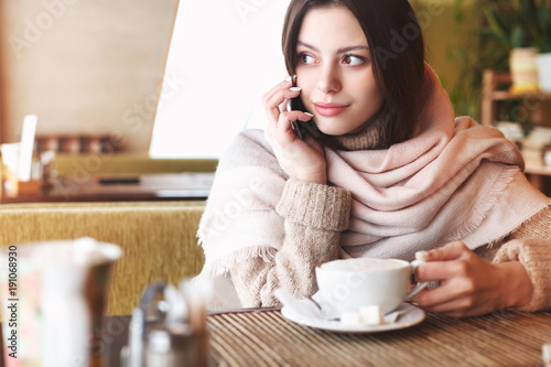Beautiful young girl using phone in cafe