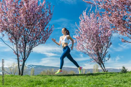 Aluminium Hardlopen Frau macht Fitness Jogging auf Hügel zwischen Kirschbäumen die blühen
