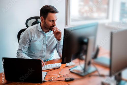 Concentrated businessman analyzing graphs in his office at computer. © bnenin