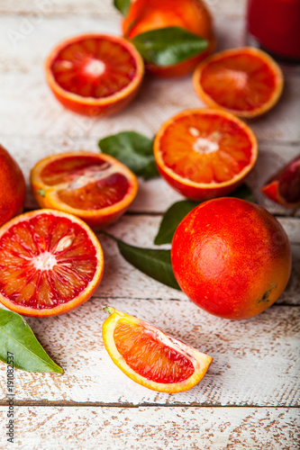 Foto Murales Bloody red oranges slices with leaves on wooden background