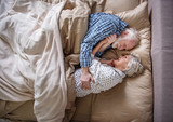 I love you. Top view of glad senior husband and wife sleeping in bedroom. They are hugging and looking at each other with smile - 191083138