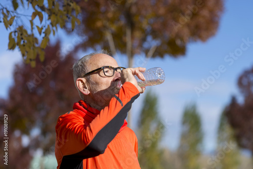 Fotobehang Hardlopen Senior runner drinking water after jogging
