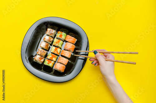 Keuken foto achterwand Sushi bar Female hand with chopsticks and plate with various rolls. Yellow background. Top view