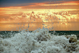 A foamy wave splash in front of sunset cloudy golden sky - 191090384