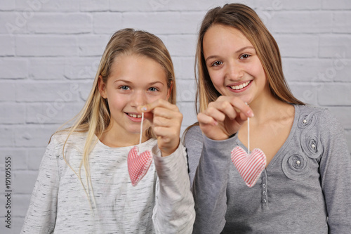 Portrait of two cute smiling sisteteenage girls holding handmade heart shape decorations. Love, Happy family, togetherness concept